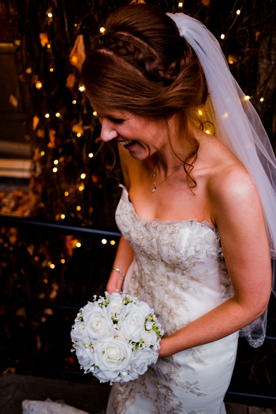 Photography of bride laughing, wearing Slim white dress with bouquet