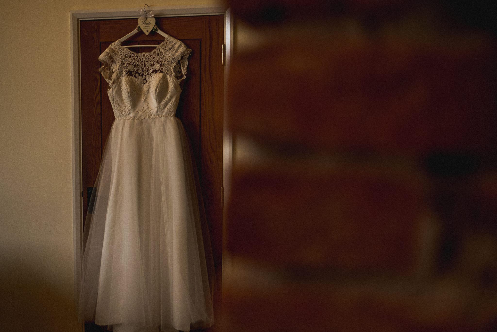 Bridal gown hanging on barn doorway