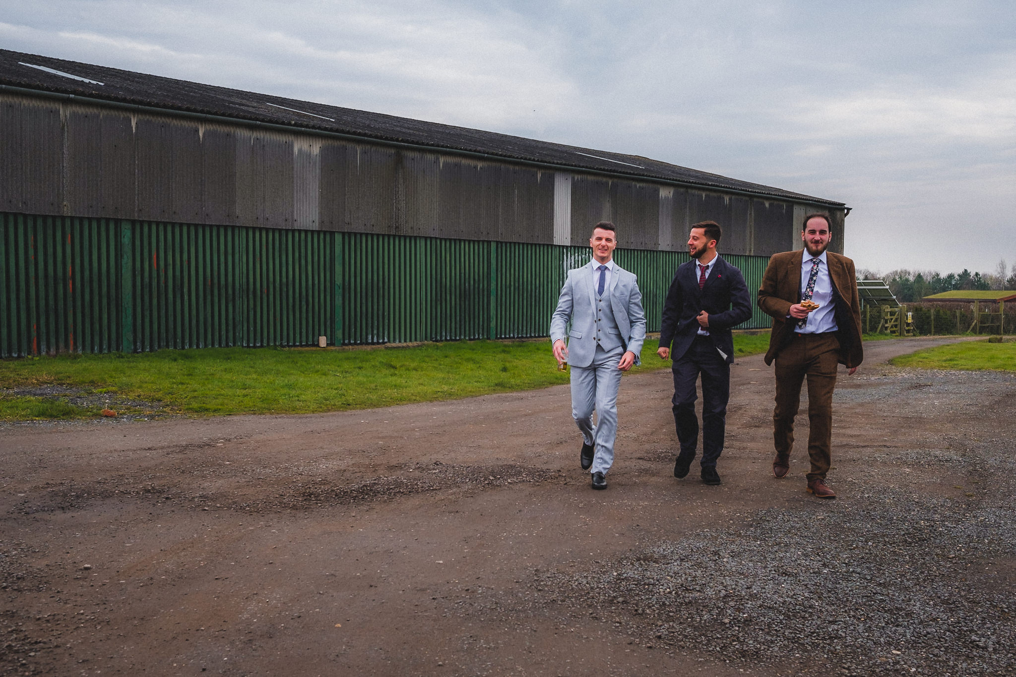 Candid wedding photography of groomsmen getting ready in style for wedding at Berts Barrow Farm