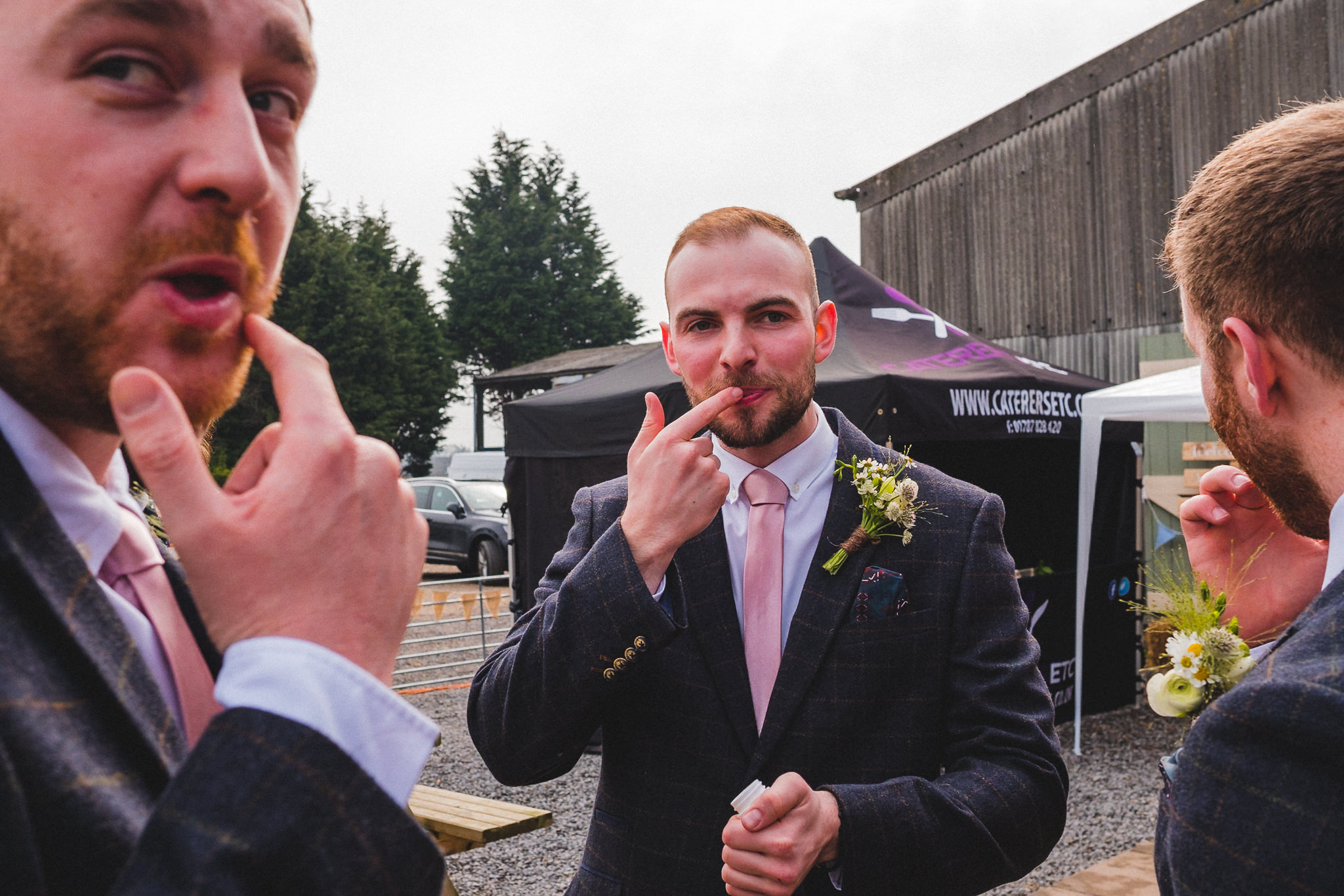 Candid photo of groomsmen applying beauty products