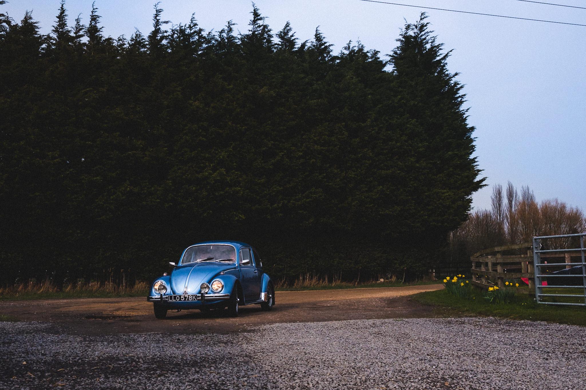 Quirky bride in Vintage Beetle wedding car arriving at Berts Barrow farm