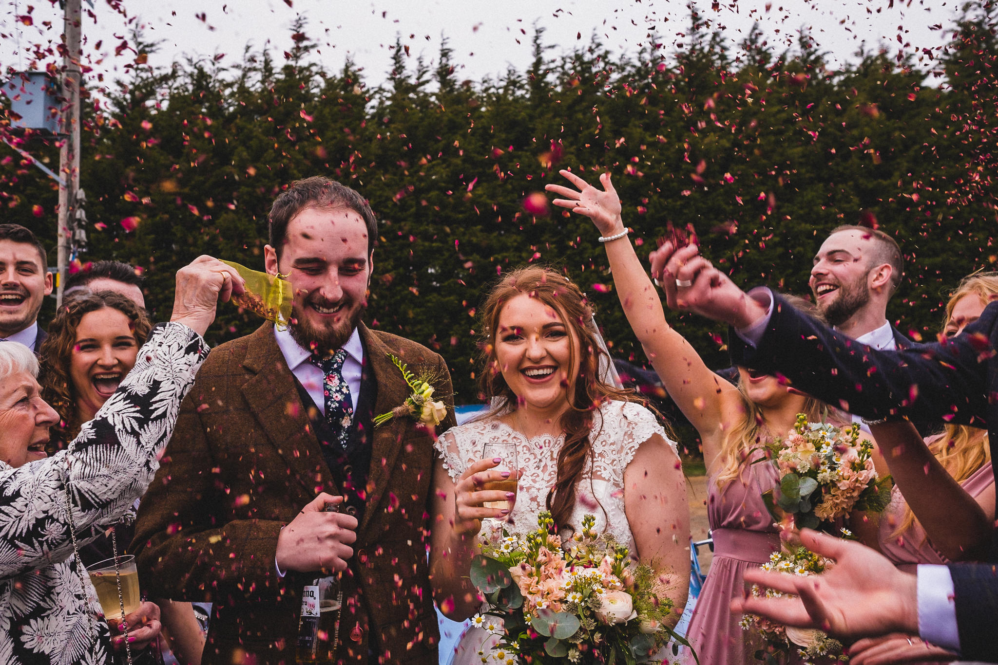 Organic biodegradable confetti being thrown over alternative bride and groom