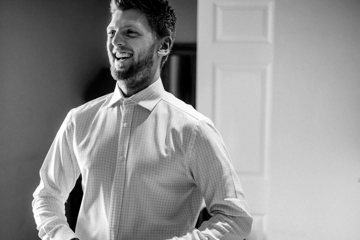 Wedding photography of Groom Laughing in the Lake District