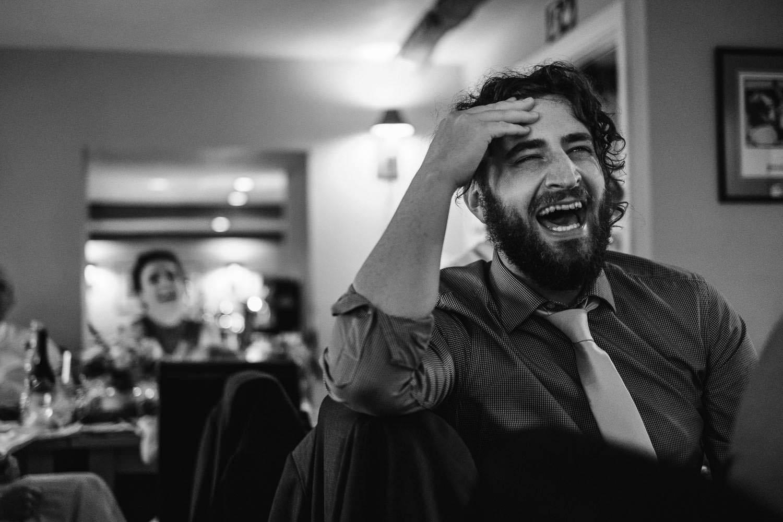 Groomsman laughing at groom speech