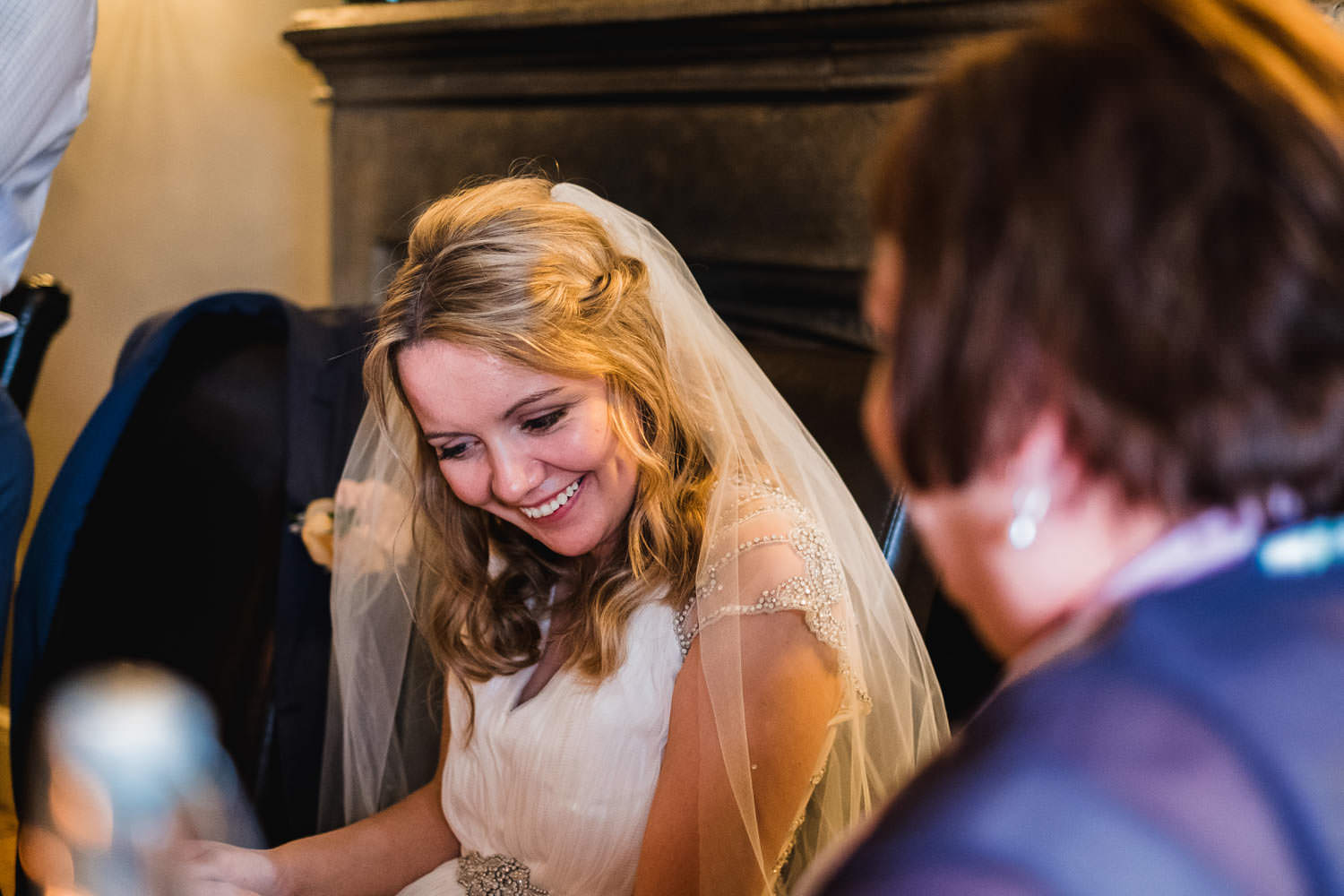 Candid photograph bride smiling at groom speech