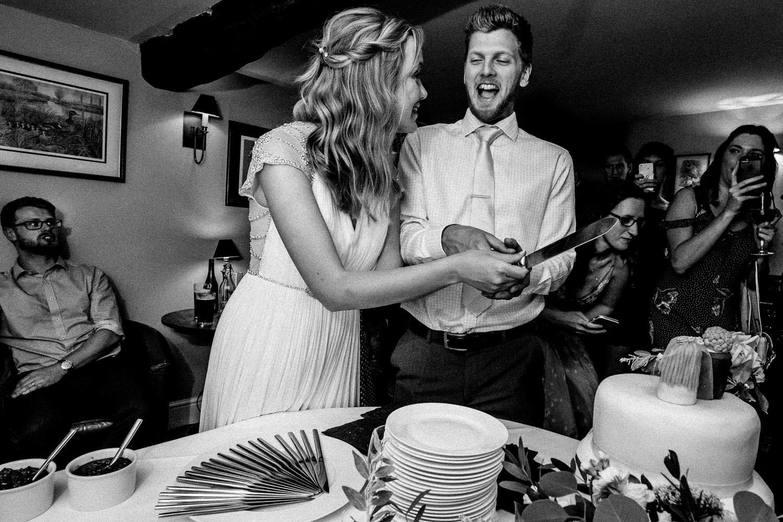 Bride and groom cutting homemade wedding cake